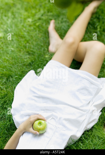 Woman lying in grass, holding apple, low section Stock Foto