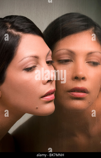 Young Hispanic woman and her mirror reflection Stock Foto