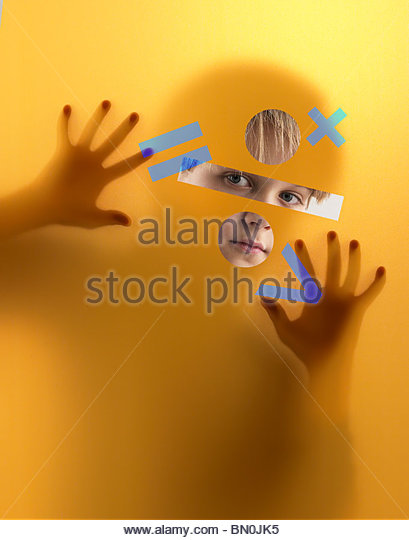 A boy peers through a screen covered in mathematics symbols Stock Foto