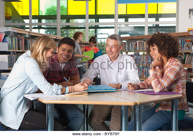 teacher-helping-in-study-group-with-stud