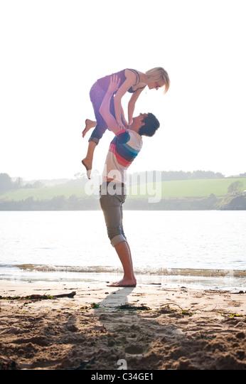 Man lifting girl on summer beach, loving Stock Foto