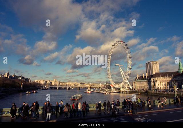 View over the River Thames, London Eye and pedestrians walking along Westminster Bridge, London, England, United Stock Photo