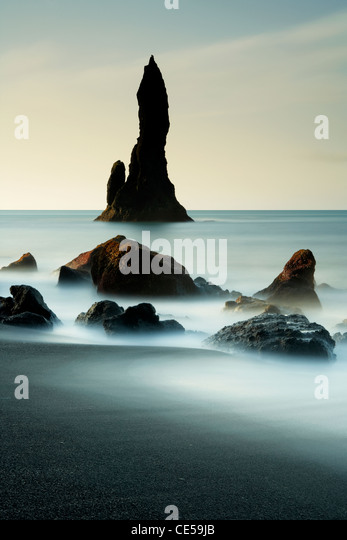 Waves washing in around black volcanic sea stacks on the Vik coast in Iceland Stock Foto