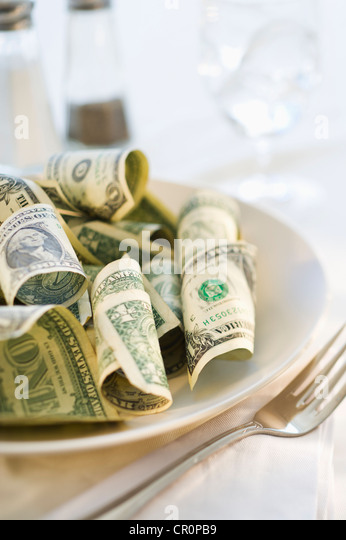 Paper currency on dinner plate, studio shot Stock Foto