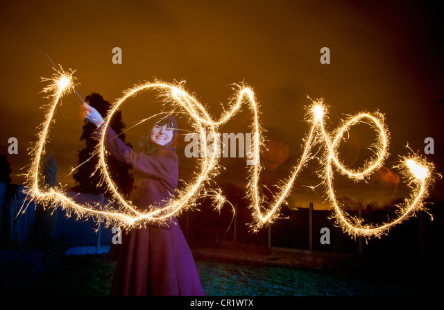 Woman writing LOVE with sparkler Stock Foto