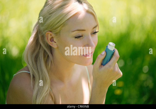 a-young-blond-woman-sitting-in-the-grass