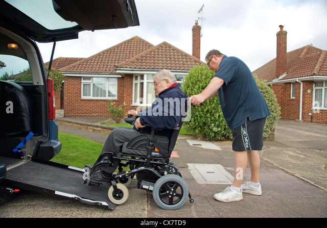 Male Carer son pushing a disabled elderly man in a wheelchair onto a built in ramp in a specially adapted car for Stock Foto