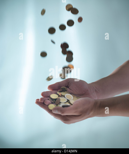 Close up of hands catching pile of coins Stock Foto