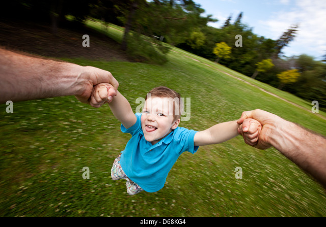 Father Spinning Son Outdoors in Park Stock Foto