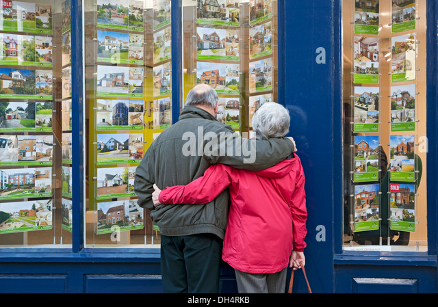 older-couple-looking-in-estate-agents-wi