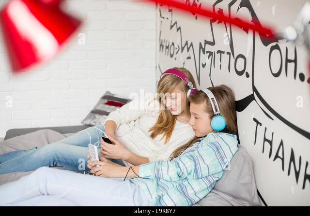 Relaxed sisters listening to music at home Stock Foto