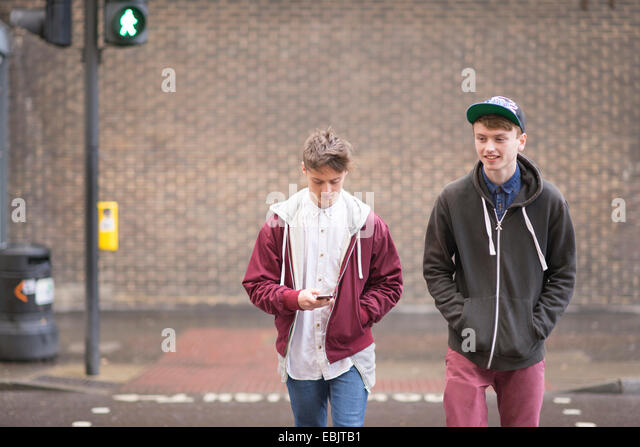 Two male friends crossing road Stock Foto