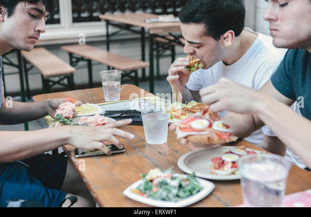 Friends having meal in public outdoor seating in New York's financial district Stock Foto