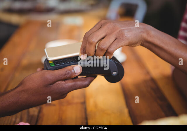 Woman paying bill through smartphone using nfc technology Stock Foto