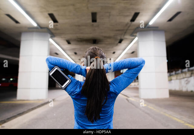 Young runner under the bridge in the evening, resting Stock Foto