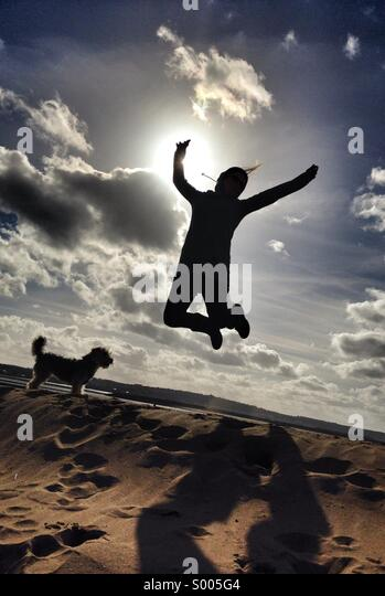 A woman jumps for joy on a sunny day at the beach in Devon, UK. Beautiful blue skies and white fluffy clouds are Stock Foto