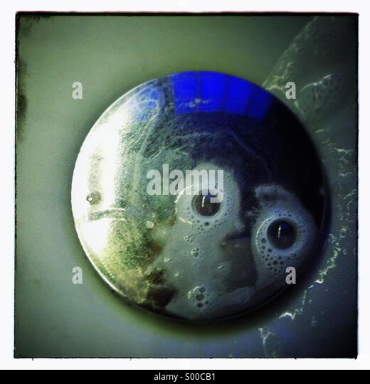 Eyes soap bubbles in a sink basin Stock Photo