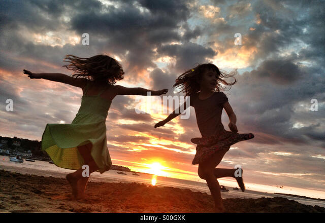 Girls whirl on the sand at sunset on the beach in devon, UK Stock Foto