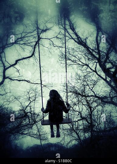 Young girl in swing in the woods Stock Foto